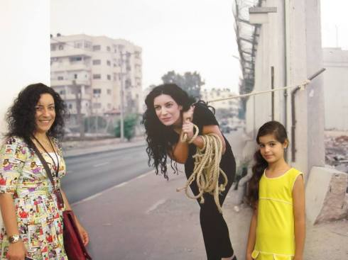 Photographer  Raeda Saadeh with one of her images at the exhibition. Photo credit: Olivia Snaije.
